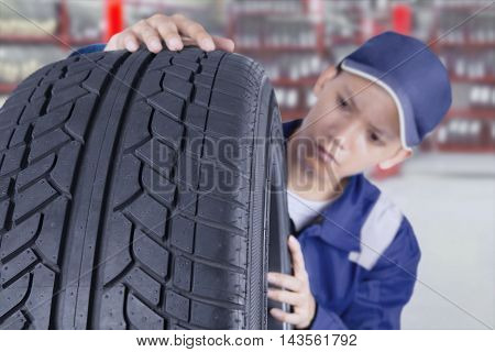 Male mechanic wearing uniform while examining tyre in the workshop