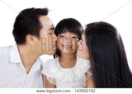 Two young parents giving their daughter a kiss isolated on white background