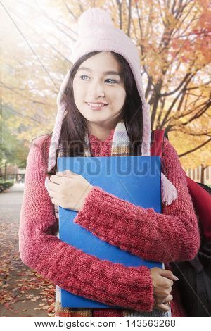 Female high school student standing at the autumn park while wearing sweater and carry bag