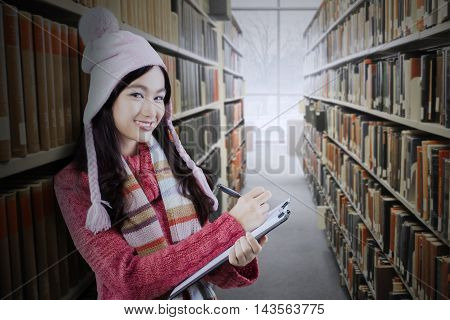 Beautiful female high school student smiling at the camera while writing on the clipboard and wearing winter clothes in the library