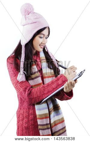 Female high school student wearing winter clothes and write on the clipboard in the studio isolated on white background