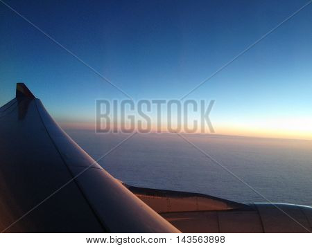 Wing of plane on beautiful sunset clouds view from window of the airplane