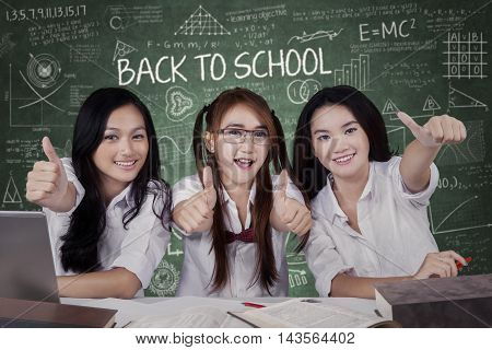 Group of three cheerful high school students back to school and showing thumbs up at the camera in the classroom