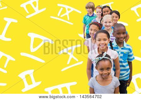 Cute pupils smiling at camera in classroom against yellow background