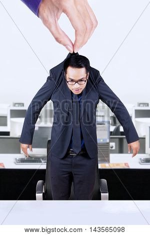 Male worker wearing formal suit and hanging on a hand in the office