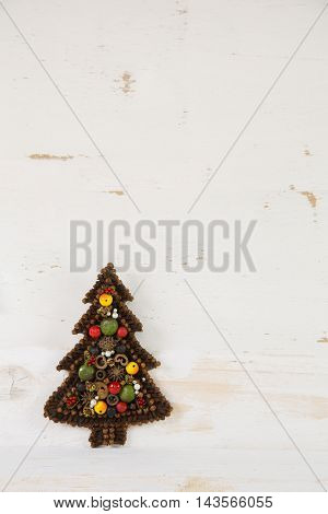 Handmade christmas tree tinkered with spicery on old wooden background.
