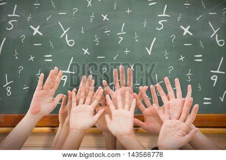 People raising hands in the air against blackboard