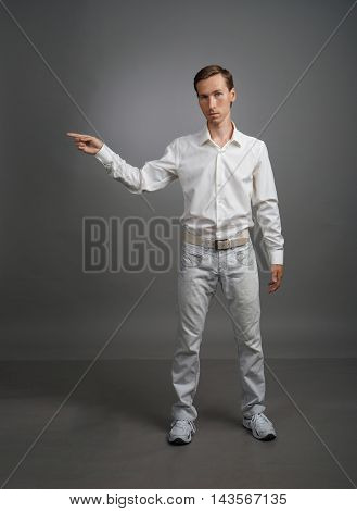 Young man in white shirt is pointing at something, standing on grey background