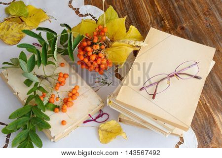 Glasses vintage books autumn leaves and rowan on the table - relax or retirement concept