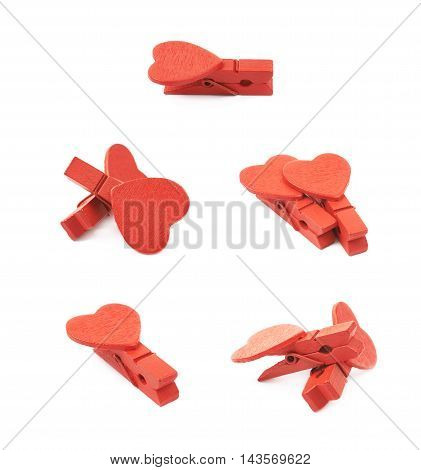 Composition of two tiny heart shaped colored wooden peg pins isolated over the white background, set of five different foreshortenings