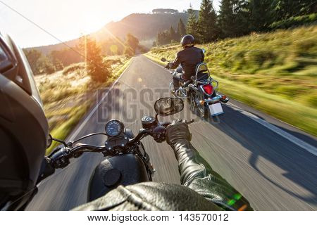 Motorcycle drivers riding on motorway in beautiful sunset light. Shot from pillion driver view