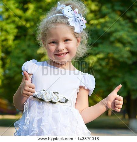 child girl portrait in white gown show best gesture, happy childhood concept, summer season in city park