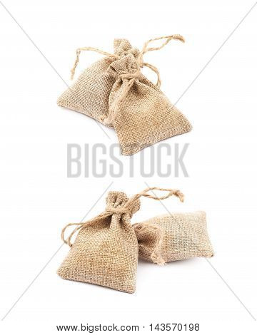 Pile of multiple tiny sackcloth bags with a tie string, composition isolated over the white background, set of two different foreshortenings