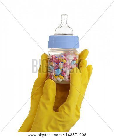 Hands in gloves holding feeding bottle full of pills on white background