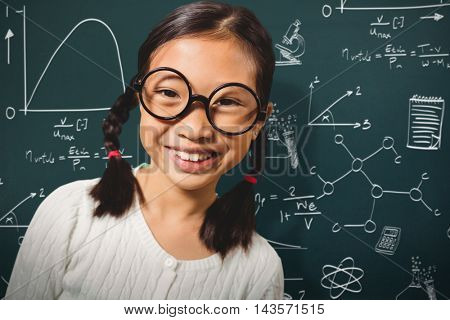 Girl smiling while standing against math and science doodles