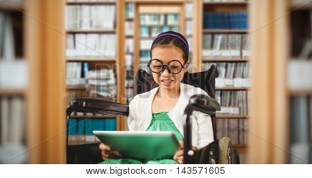 Young girl looking at digital tablet against library