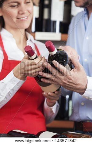 Saleswoman And Male Customer Holding Wine Bottles