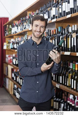 Smiling Customer Holding Wine Bottle In Store
