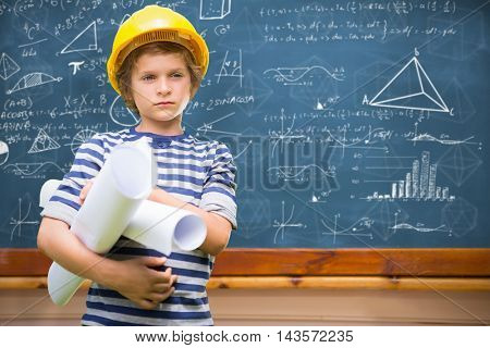 Little boy wearing yellow hat and holding plans against blackboard