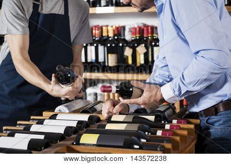 Salesman Assisting Customer In Selecting Wine Bottle At Supermar