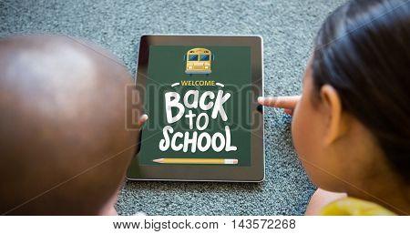 back to school against siblings using digital tablet on carpet