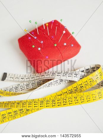 Pincushion And Measure Tape On Table At Factory