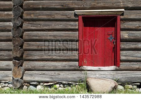 Beautiful old red door on the wooden wall of the old house. Lovely rustic background.