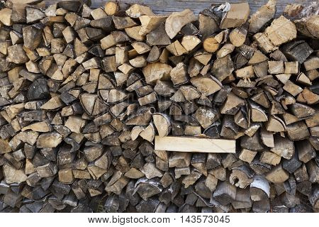 A pile of firewood at the wall of the wooden house.