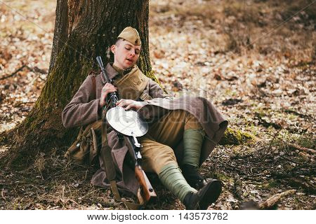 Pribor, Belarus - April 04, 2015: Young unidentified re-enactor dressed as Soviet soldier in overcoat resting under tree