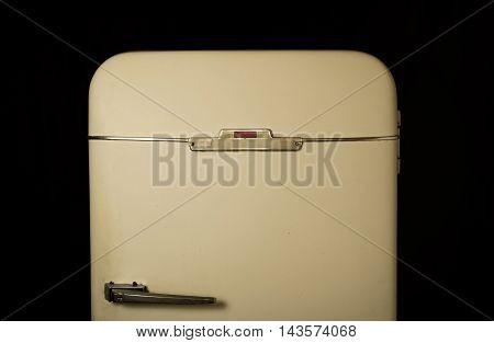 Very old fridge on a black background