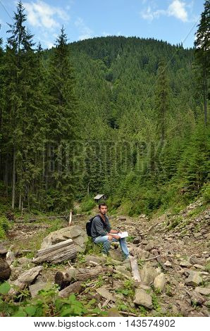 Young man in mountain valley. Pine forest, mountains