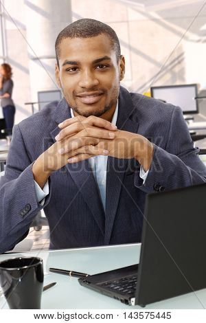 Portrait of happy afro american businessman at office. Sitting, smiling, looking at camera, in suit.