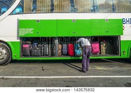Menumbok,Sabah-Aug 19,2016:The bus driver checking luggage compartment on bus in Menumbok Terminal Bus before heading to Kota Kinabalu,Sabah Land Below The Wind.