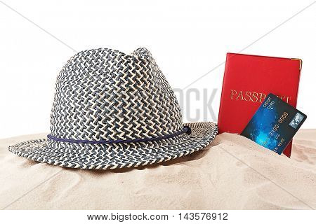 Credit card with passport and hat on the sand, white background
