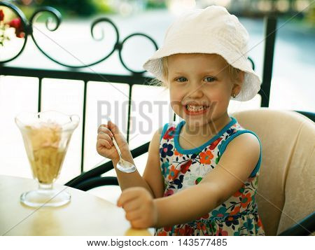 Young girl is eating icecream early in the morning.