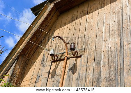 the electrocolumn with wires energized is established on a facade of the private wooden house. Summer garden Russia South Ural.