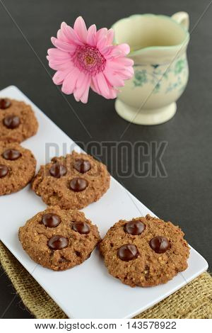 Chocolate chip cookies on black background. Decorated with pink flower