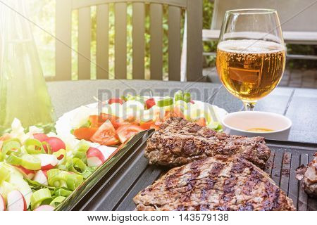 Grill steaks browned on both sides are on an electric stove. Bottle with oil various kinds of vegetables and glass of beer are standing on the table in the sunshine.