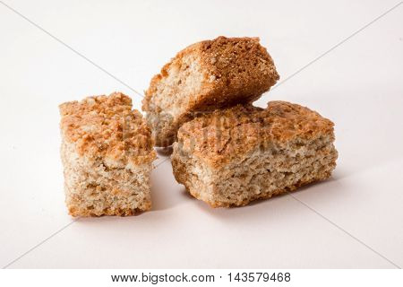 Three pieces of rusks are situated on an isolated white background with one piece resting on a second.