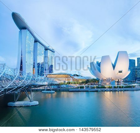 Singapore central quay with water on foreground. Modern city architecture at dusk