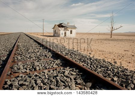 An abandoned house stand by the side of railroad tracks in the desert.