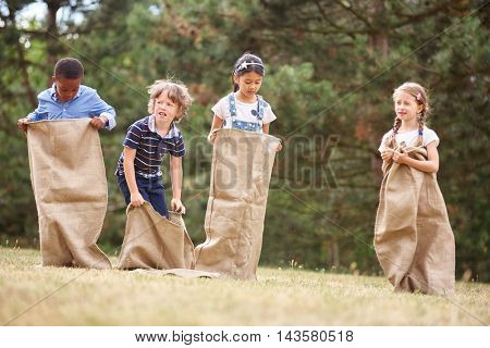 Interracial group of kids at a sack race ready to start