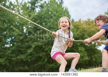 Girl and boy playing tug of war in the nature