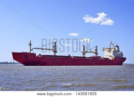 Big freight ship on a river with blue sky and copy space. Freight transportation.