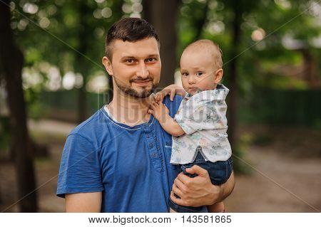 Portrait happy father and son on hands summer day in park