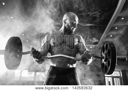 Young handsome caucasian bodybuilder sportsman working out with a barbell in gym, doing biceps training, smoke
