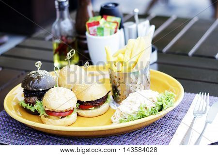 4 Sandwiches, french fries and side dish on the yellow plate.