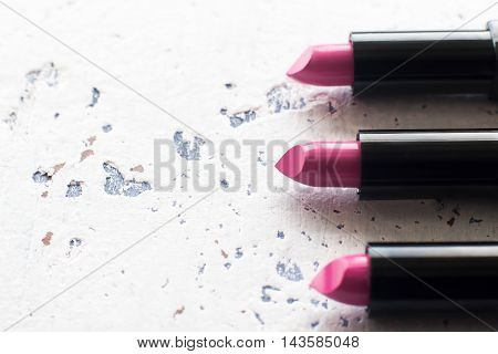 New pink lipsticks set, copy space. Top view on vertical line of three rosy rouge on light textured background. Great photo for cosmetics catalog, free space for text or commercials