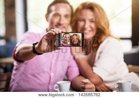Digital world. Close up of screen of mobile phone with a photo of smiling couple on it