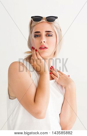 Relaxed woman after face massage, close-up. Sensitive blonde in sunglasses touching her face and looking satisfied, white background